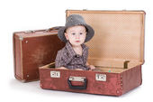 The small smiling boy sits in an open road suitcase. — Stock Photo