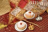 Hanukkah menorah with dreidel and doughnuts — Stock Photo