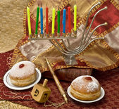 Hanukkah menorah with candles and doughnuts — Stock Photo