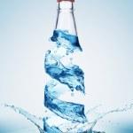 Bottles in water swirl — Stock Photo