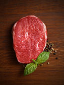 Fresh raw steak with pepper and basil — Stock Photo
