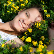 Portrait of a smiling beautiful girl in the yellow flowers — Stock Photo