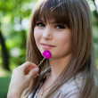 Portrait of beautiful young girl in park with flower in hand — Stok Fotoğraf #7679481