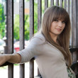 Young beautiful girl at the fence — Stockfoto