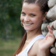 Portrait of a smiling beautiful girl with a stone wall - Stockfoto