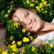 Portrait of a smiling beautiful girl in the yellow flowers - Stockfoto