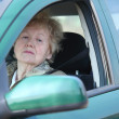 Elderly woman looks in car - Stock Photo