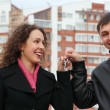 Young couple with key against many-storeyed house — Stock Photo #7424342