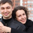 Young pair embraces and smiles against building - Stock Photo