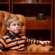 Boy sits in leather armchair in luxury office — Stock Photo