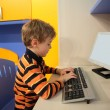 Boy at computer in children's room — Stockfoto