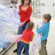 Young woman with children in shop of textile — Stock Photo