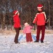 Mother and father with daughter in wood in winter — Stock Photo #7424776