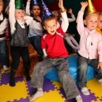 Children on holiday in kindergarten with raised hands — Stock Photo