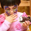 Stock Photo: Little girl painted for holiday eats cake