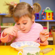 Little girl eats in kindergarten - Stock Photo