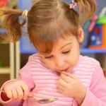 Little girl eats in kindergarten — Stock Photo