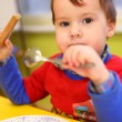 Little boy eats in kindergarten — Stock Photo