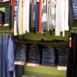 Shelves and racks with clothes in shop — Stock Photo