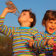 Two children in striped T-shirts, boy drinks from bottle, gir — Stock Photo