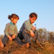 Little girl and boy with bottle and stick in striped t-shirts si — Stock Photo