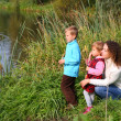 Mother with children sits on bank of pond — Stock Photo