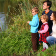 Stock Photo: Parents with children sits on bank of pond