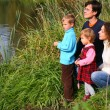 Parents with children sits on bank of pond — Stock Photo