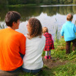 Parents with children sits on bank of pond, rear view — Stock Photo