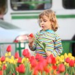 Little girl in striped t-shirt and tulips on street — Stock Photo #7425188
