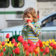Little girl in striped t-shirt and tulips on street — Stock Photo