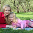 Mother with daughter lie on grass in park in spring — Stock Photo