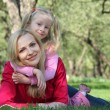 Daughter embraces behind mother lying on grass in park — Stock Photo