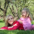 Stock Photo: Daughter has leant elbows on mother lying on grass in park