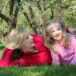 Mother embraces daughter lying on grass in park — Stock Photo #7425231