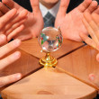 Three pairs hands and glass globe on stool — Stockfoto