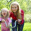 Laughing girl on bicycle with mother in spring garden — Stock Photo