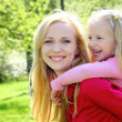 Laughing daughter sits at mother on  back in spring park — Stock Photo