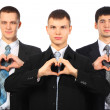 Three young businessmen show love sign from hands - Stock Photo