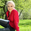 Beautiful blonde sits on grass in garden in spring — Foto de Stock