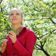 Beautiful blonde looks upward in blossoming garden in spring — Stock Photo #7425374