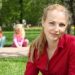 Beautiful blonde in park with playing children on background — Stock Photo