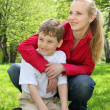 Stock Photo: Mother embraces behind son sitting in lap on grass in park in