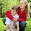 Mother embraces behind son sitting in lap on grass in park in — Stock Photo #7425430