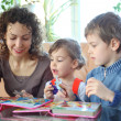 Mother and children play with jigsaw puzzle — Stock Photo