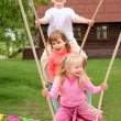 Three children on  swing - Stock Photo