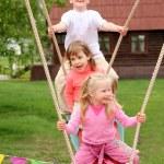 Three children on swing — Stock Photo