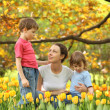 Mother with children in garden in spring among blossoming tulips — Stock Photo