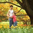 Son embraces mother in garden in spring among blossoming tulips — Stock Photo