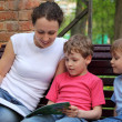 Mother with children sit on bench and read book — Stock Photo #7425619